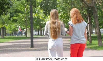 Beautiful teenage girls having fun in spring park, slow...