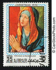 postmark - AJMAN - CIRCA 1970: Ancient picture Maria prays ,...