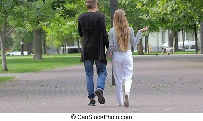 Couple in love walking together hand by hand in park slow...