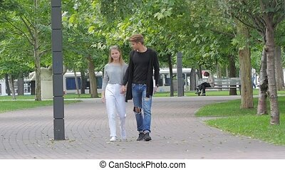 Couple in love walking together hand by hand  in park. slow motion