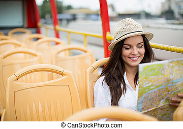 Tourism - Young girl with a map of on a bus