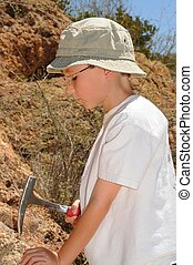 Boy Geologist - Boy geologist tap a rock formation with a...