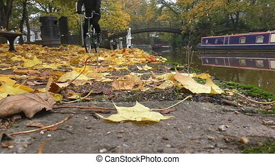 Cyclists on canal side in autumn - Low angle view of a...