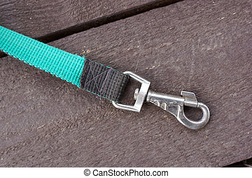 Part dog leash with carabiner. On a wooden surface....
