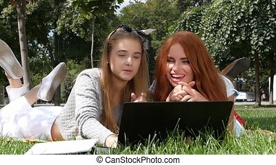 Girls using wifi internet in college park. slow motion