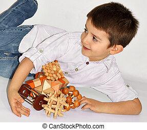 Wooden Brain Teaser - Joyful boy with many wooden logic toys