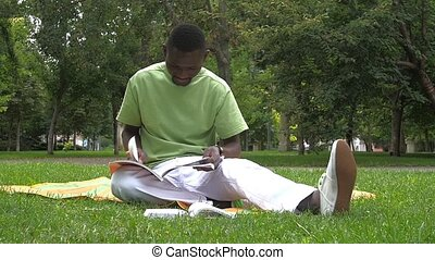 African-American man writes in a notebook at the park, slow...