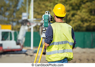 Surveyor engineers working with theodolite on road...