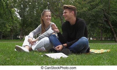Happy Smiling Couple in love of students Relaxing on Green Grass. slow motion