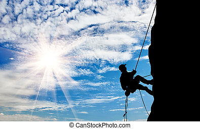 Silhouette climber climbing a mountain - The concept of...