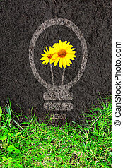 Eco background with green grass and light bulb silhouette