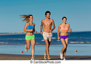Group of sport people - man and women - jogging on the beach