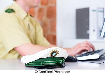 Police Officer working on desk in station - Police officer...
