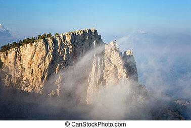 Clouds move below rocks on the mountain Ai Petri, the Crimea