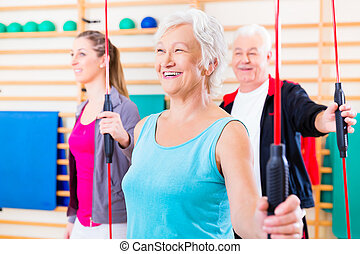 Group at fitness training with gymnastic bar, young and...