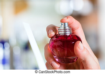 woman buying perfume in shop or store