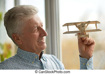 man with wooden plane - Senior man with wooden plane at home...