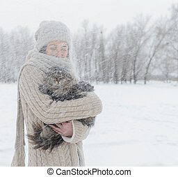 Woman with a cat outdoors - Young woman holds a cat outdoors...