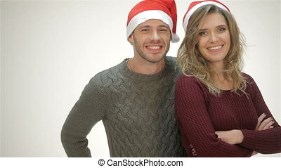 Cheerful couple in Santa hat laughs while standing in an...