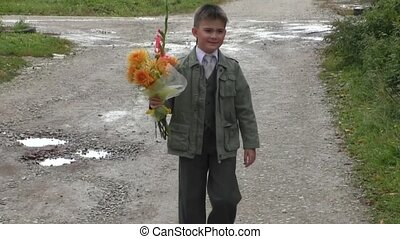 The boy goes with a bouquet of orange dahlias