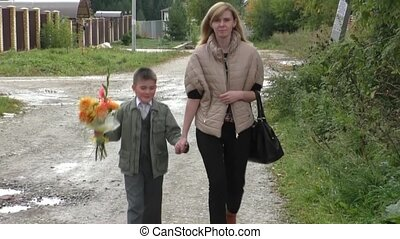 Mother and son go on the road with a bouquet of Orange...
