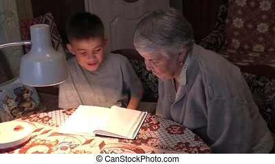 The prograndmother with the great-grandson read at the table...