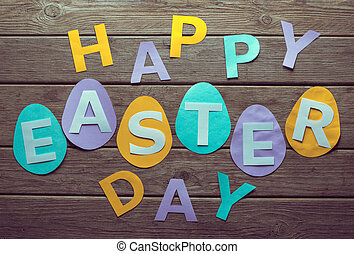 Inscription Happy Easter day on paper eggs on a wooden table