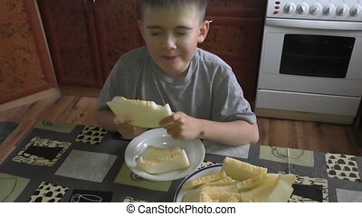 The boy eats melon - The boy eats an appetizing tasty melon