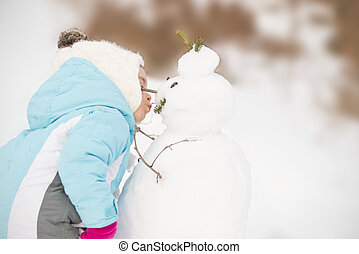 Child sharing affection to snowman - Funny little girl in...