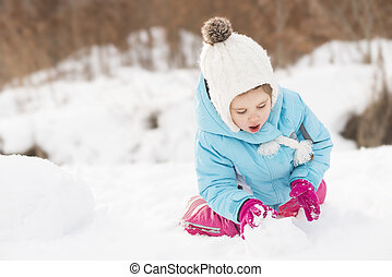 Kid playing outdoors in winter - Funny little girl in a warm...
