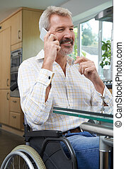 Disabled Man In Wheelchair Making Call On Mobile Phone At Home