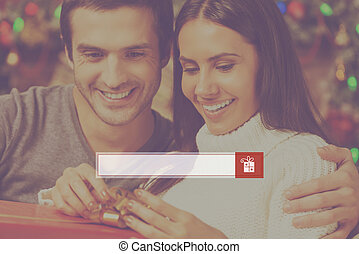 Presents search. Happy young woman opening a gift box while her boyfriend sitting close to her and smiling with Christmas decoration in the background