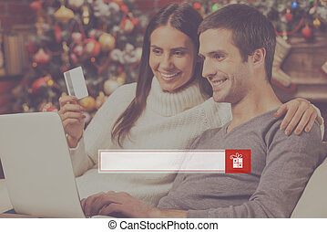 Find presents online Beautiful young couple buying online...