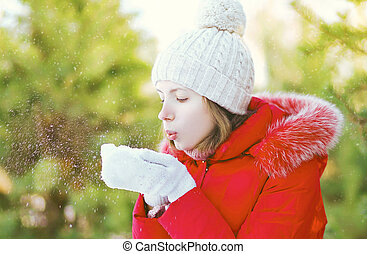 Girl blowing on snow in hands, winter day