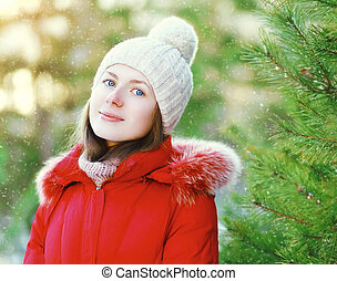Portrait cute smiling young girl wearing a red jacket and hat in winter day