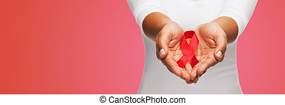 close up of hands with red AIDS awareness ribbon -...