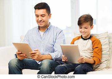 happy father and son with tablet pc at home - leisure,...