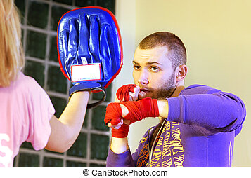 kickboxer - young adult man boxing in gym with his trainer