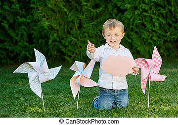 little boy playing in the park on the grass with windmills