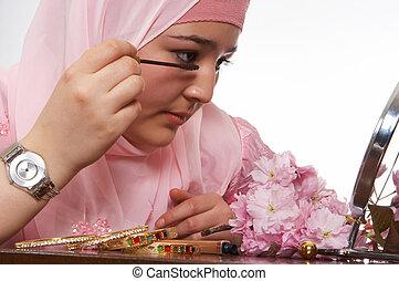 Veiled beauty - Young islamic beauty applying mascara to her...