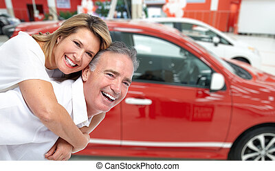 Happy senior couple near new car.
