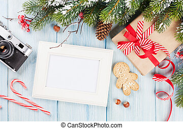 Christmas photo frame on wooden table with tree, camera and...