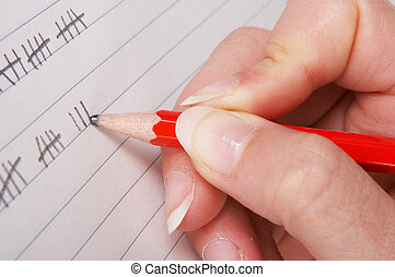 Tally paper - Hand holding a pencil and counting scores