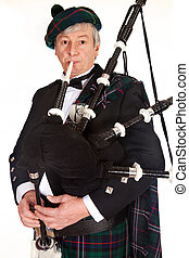 Bagpiper in tartan - Scottish highlander wearing kilt and...