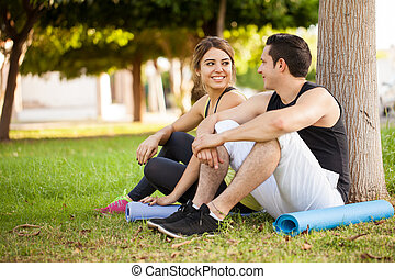 Sporty couple relaxing at a park - Good looking young couple...