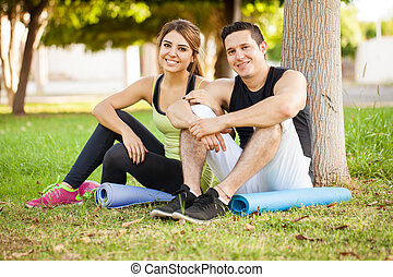 Cute athletic couple at a park - Portrait of a young...