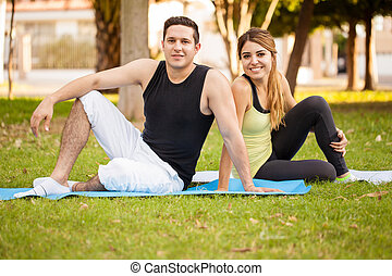 Couple taking a break from yoga - Cute Hispanic young couple...