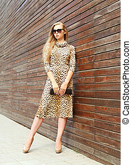 Fashion beautiful woman wearing a leopard dress and...