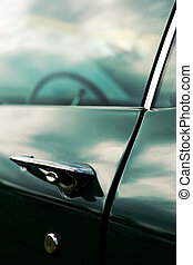 Chrome handle and lock on a green door - Sky reflection on a...