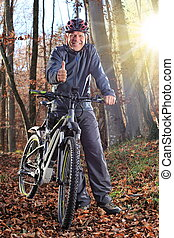 Senior with e-bike MTB and thumb up - A Senior with e-bike...
